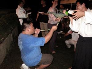 Budo should be fun! A student enjoys sake through a lotus stalk after hard practice.